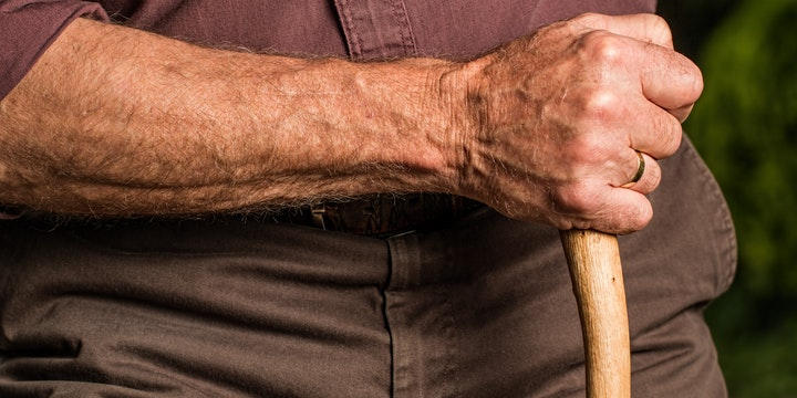 Man with mobility issues holding walking stick